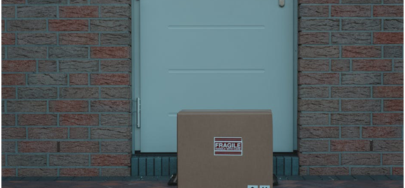 The outside view of a home's door with a package placed in front of it